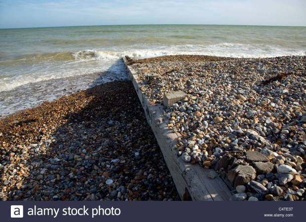 Longshore drift illustrated by sediment either side of wooden groyne on shingle beach