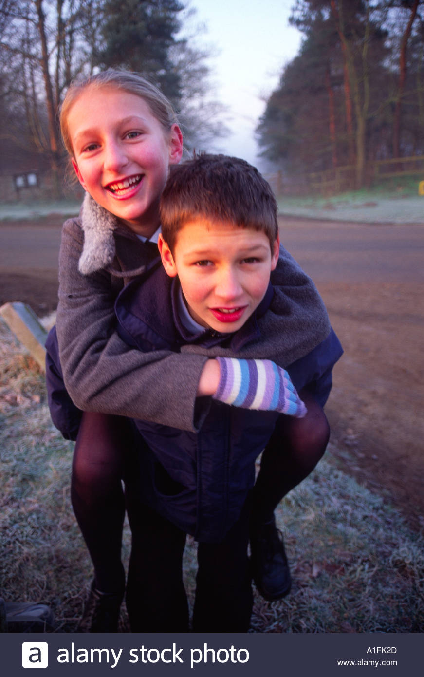 Brother giving twin sister a piggyback ride UK